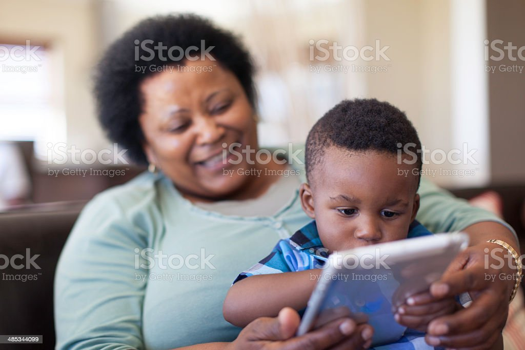Grandmother teaching her grandson how to read. stock photo