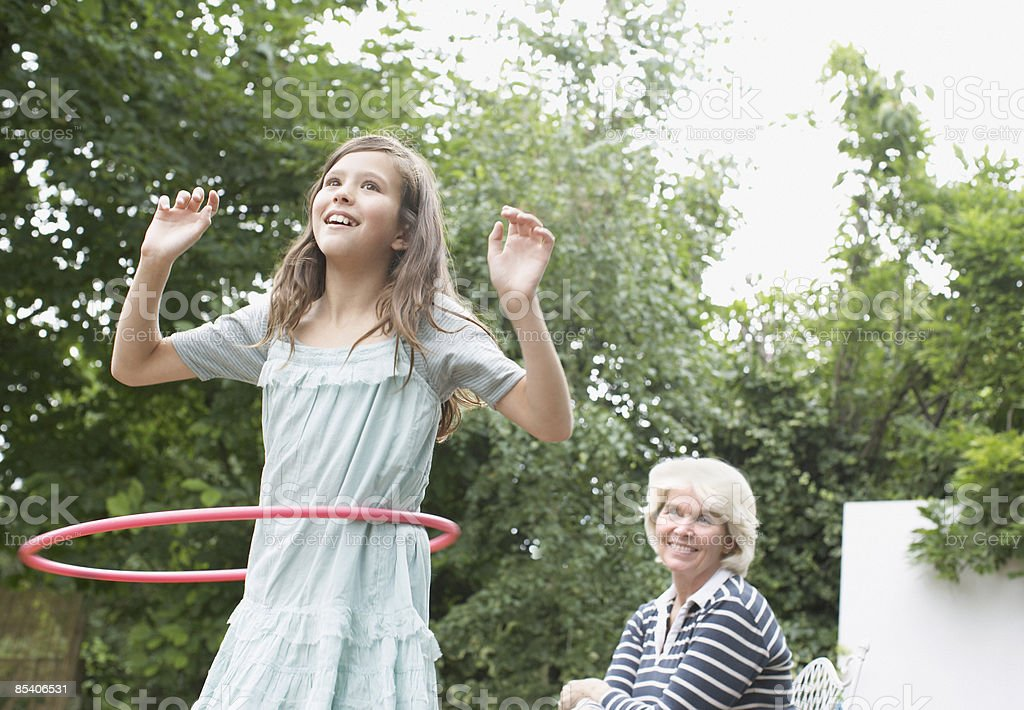 Grandmother watching granddaughter with hula hoop royalty-free stock photo