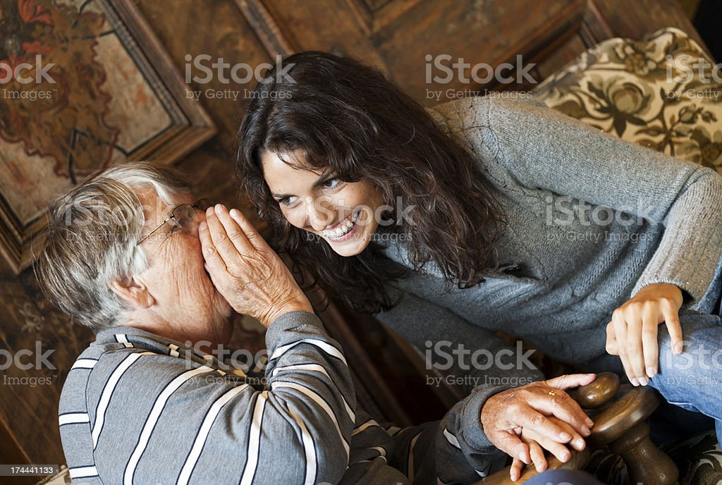 Grandmother whispering to a woman royalty-free stock photo