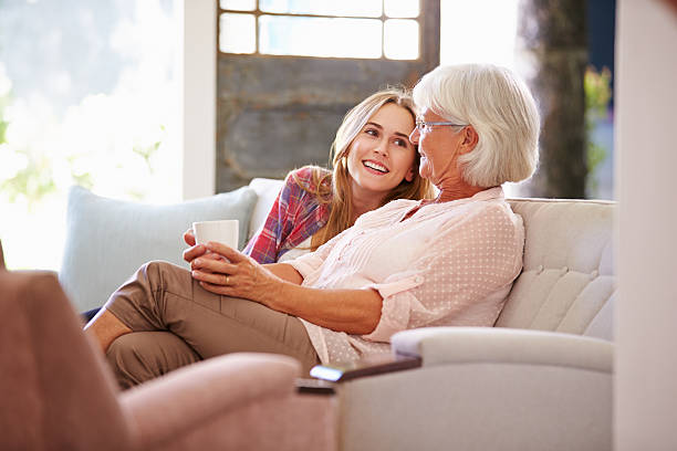 grandmother with adult granddaughter relaxing on sofa - granddaughter and grandmother stock photos and pictures
