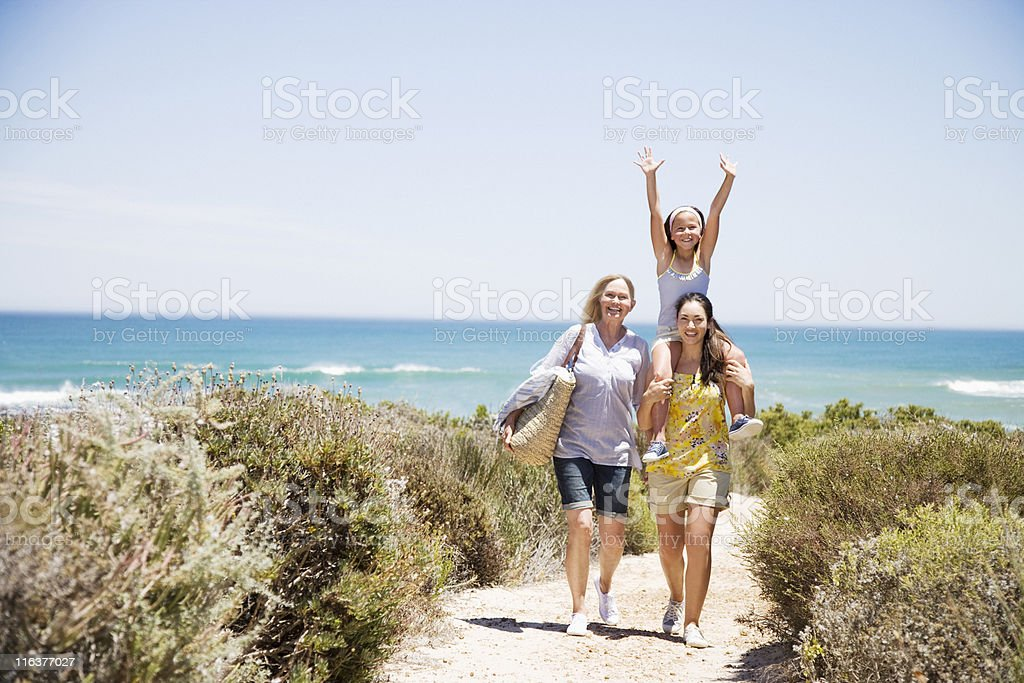 Grandmother with daughter and granddaughter on beach path stock photo