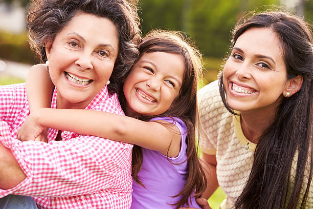 grandmother with granddaughter and mother in park - granddaughter and grandmother stock photos and pictures