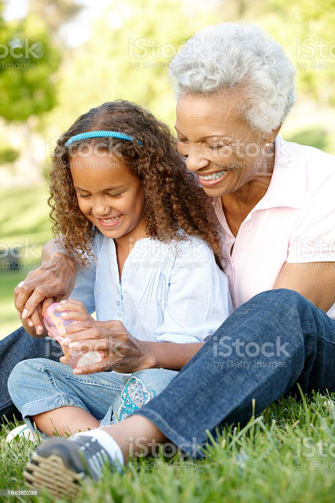 Grandmother with granddaughter blowing bubbles in the park  royalty-free stock photo