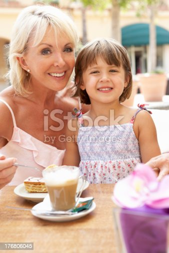 Grandmother With Granddaughter Enjoying Coffee And Cake In Caf