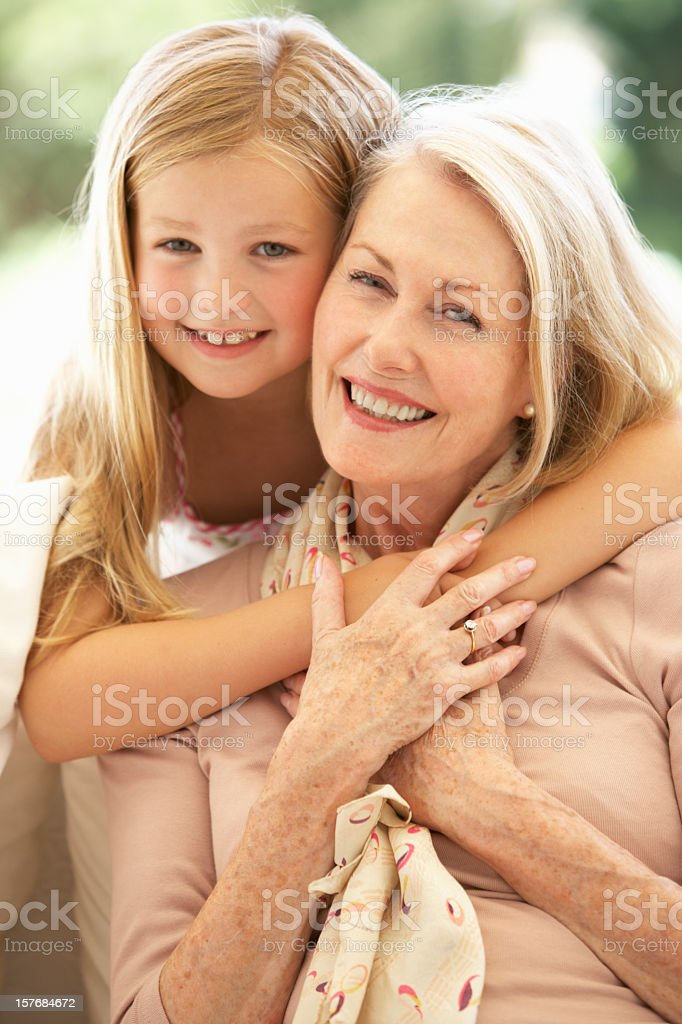 Grandmother With Granddaughter Laughing On Sofa royalty-free stock photo