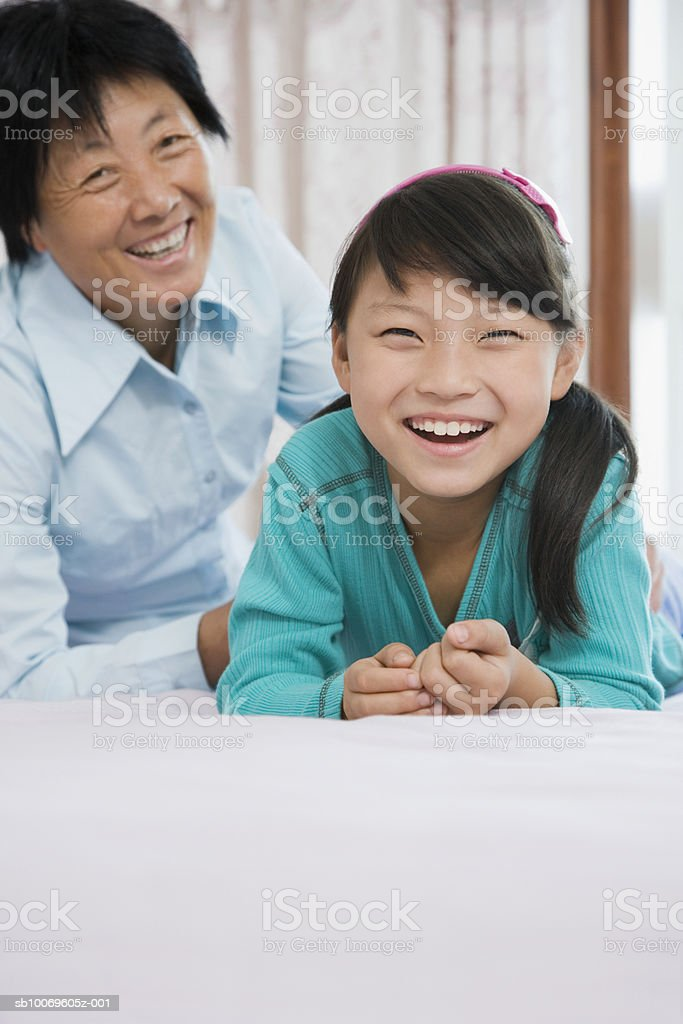 Grandmother with granddaughter (8-9) on bed, smiling, portrait foto royalty-free