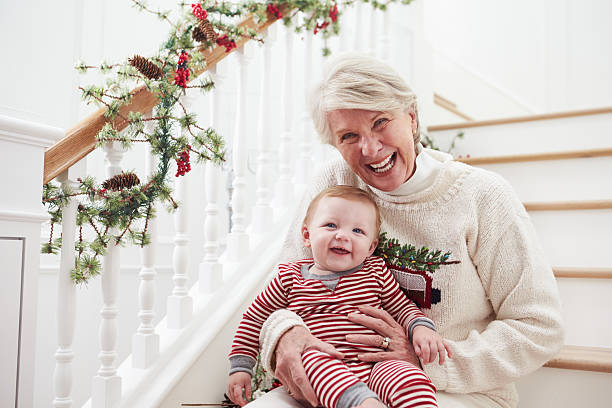 grandmother with granddaughter sits on stairs at christmas - christmas tree stockfoto's en -beelden