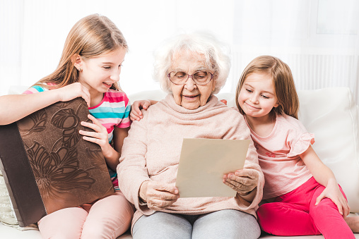 Grandmother with little granddaughters reading letter together