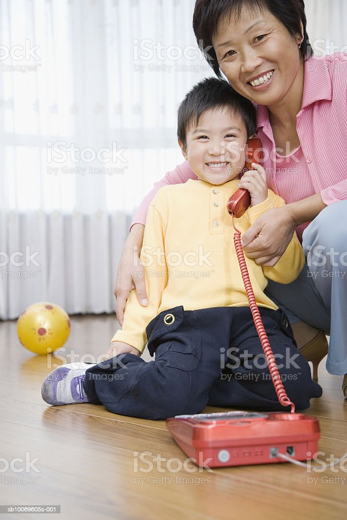 Grandmother with grandson (4-5) smiling, boy talking on telephone royalty-free stock photo