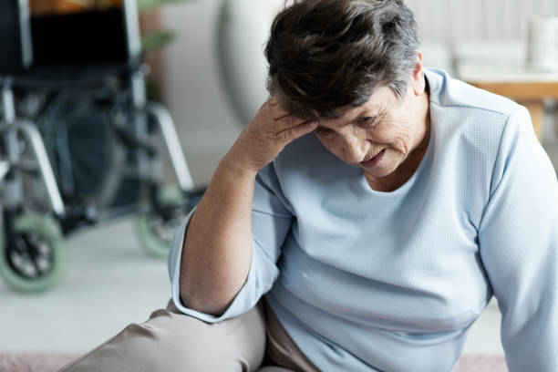 Grandmother with headache fell to the floor in the nursing house stock photo