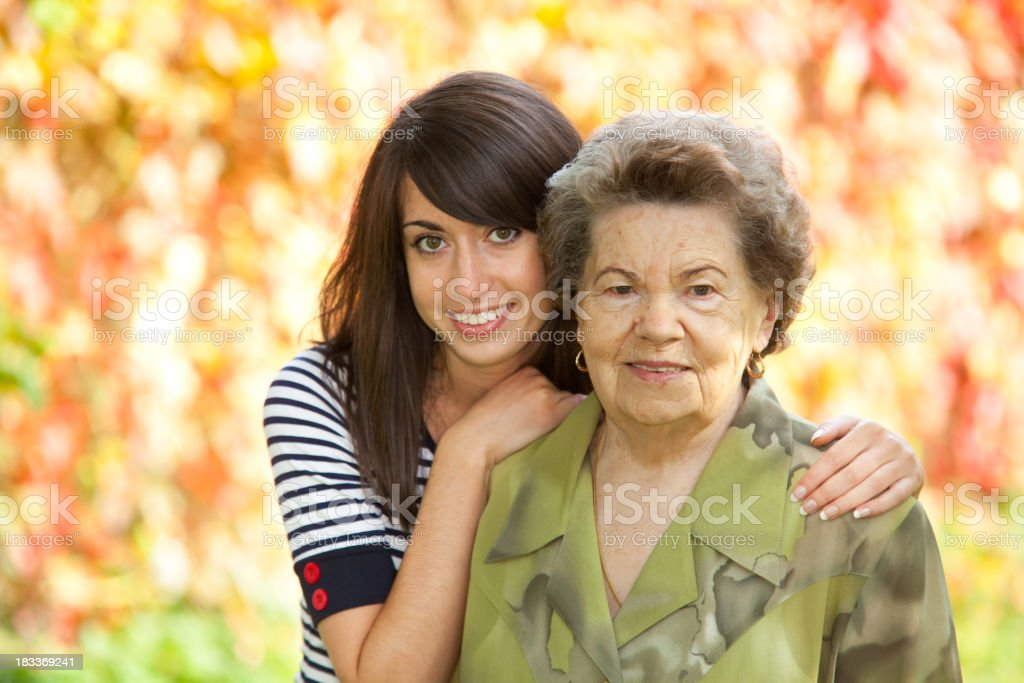 Grandmother with her granddaughter against defocused multicolored leaves royalty-free stock photo