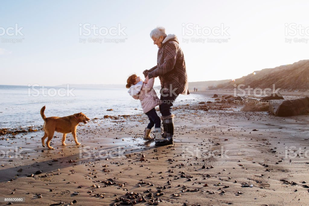 Grandmother with her Granddaughter on the Beach stock photo