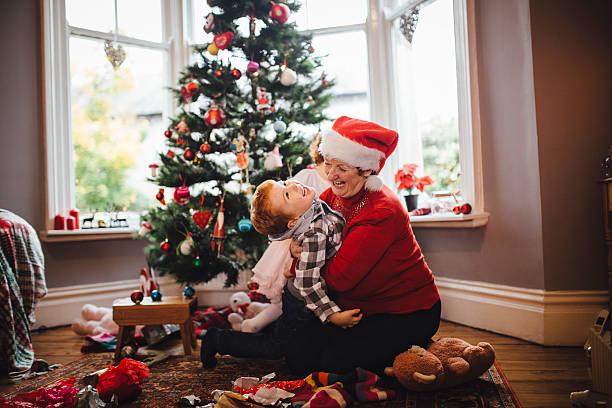 grandmother with her grandson on christmas day - alte weihnachtsbäume stock-fotos und bilder