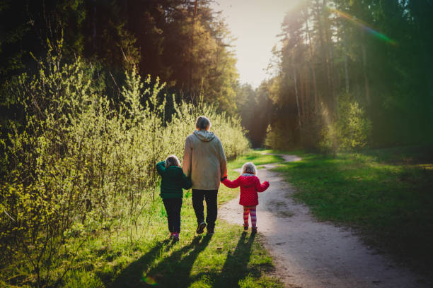 Großmutter mit Kindern spazieren in der Natur bei Sonnenuntergang – Foto