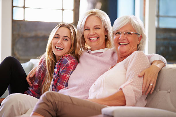 grandmother with mother and adult daughter relaxing on sofa - three people stock photos and pictures