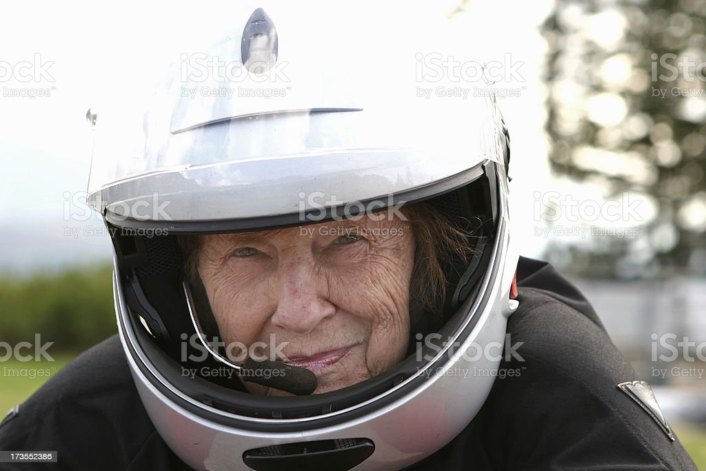 Grandmother with motorcycle helmet stock photo