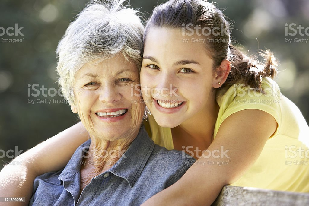 Grandmother With Teenage Granddaughter Sitting On Bench Together stock photo