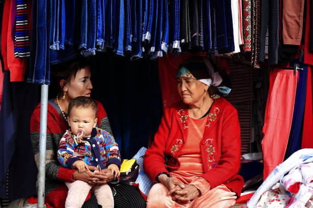 Großmutter-Mutter-Mutter-Enkel im Chat in einem Stall, in dem Kinderkleidung verkauft wird, Hotan Sonntag Markt-Xinjiang-China-0103 – Foto