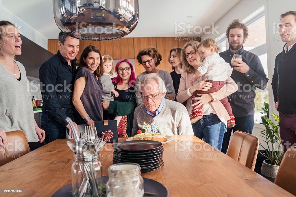 Grandpa 75th birthday celebration with three generation family at home. stock photo