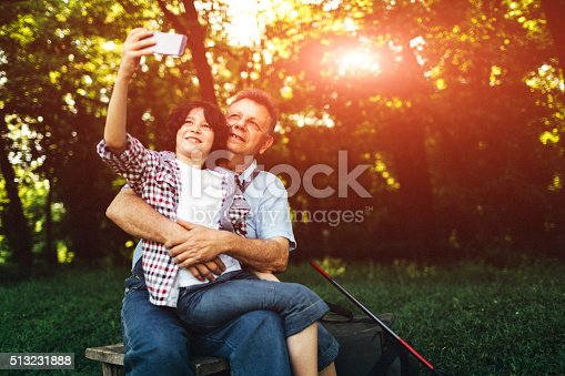 992209122 istock photo Grandpa and grandson fishing together and making selfie. 513231888