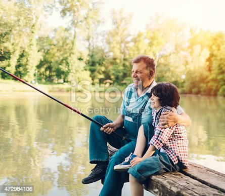 483319252 istock photo Grandpa and grandson fishing together. 472984106
