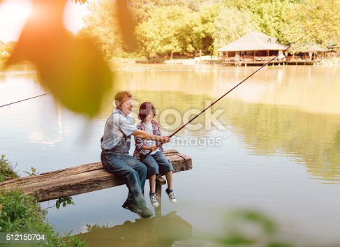 483319252 istock photo Grandpa and grandson fishing together. 512150704