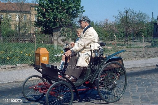 Marienfelde, Berlin West, Germany, 1975. Grandpa and grandson on a Benz Motor Velociped from 1894 on the way to a vintage car parade.