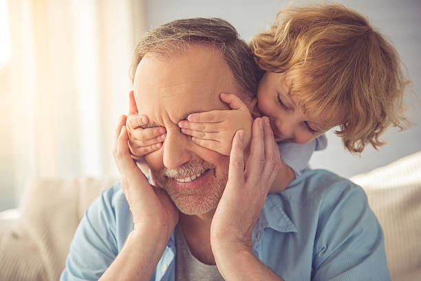 Grandpa and grandson Cute little boy is covering his grandpa's eyes and smiling while playing with him at home grandson stock pictures, royalty-free photos & images