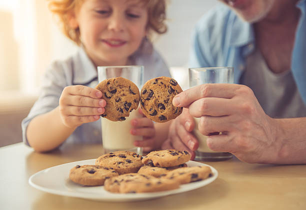 Grandpa and grandson Cropped image of handsome grandpa and grandson drinking milk and eating cookies together at home cookie stock pictures, royalty-free photos & images