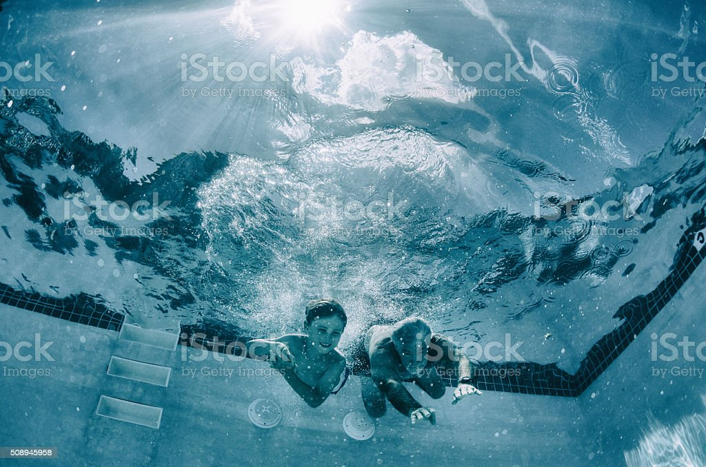 Grandpa and grandson race underwater in a pool stock photo