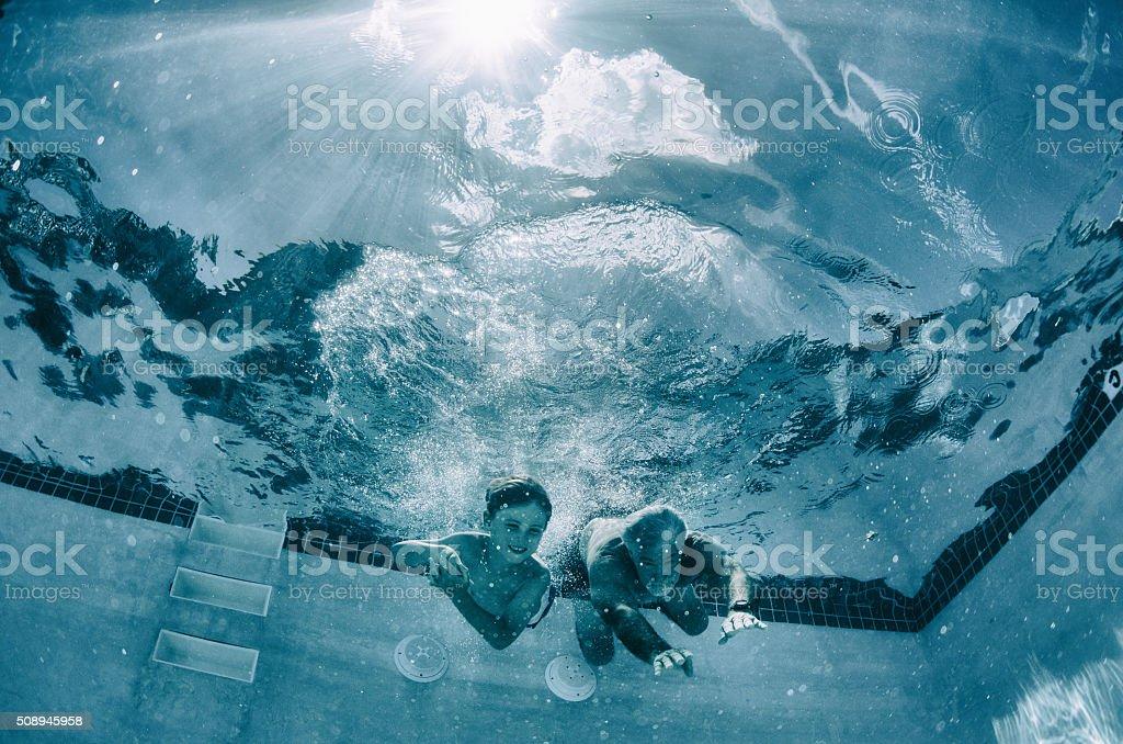 Abuelo y nieto raza bajo el agua en la piscina - foto de stock