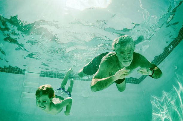 Grandpa and Grandson swimming together underwater in summer stock photo