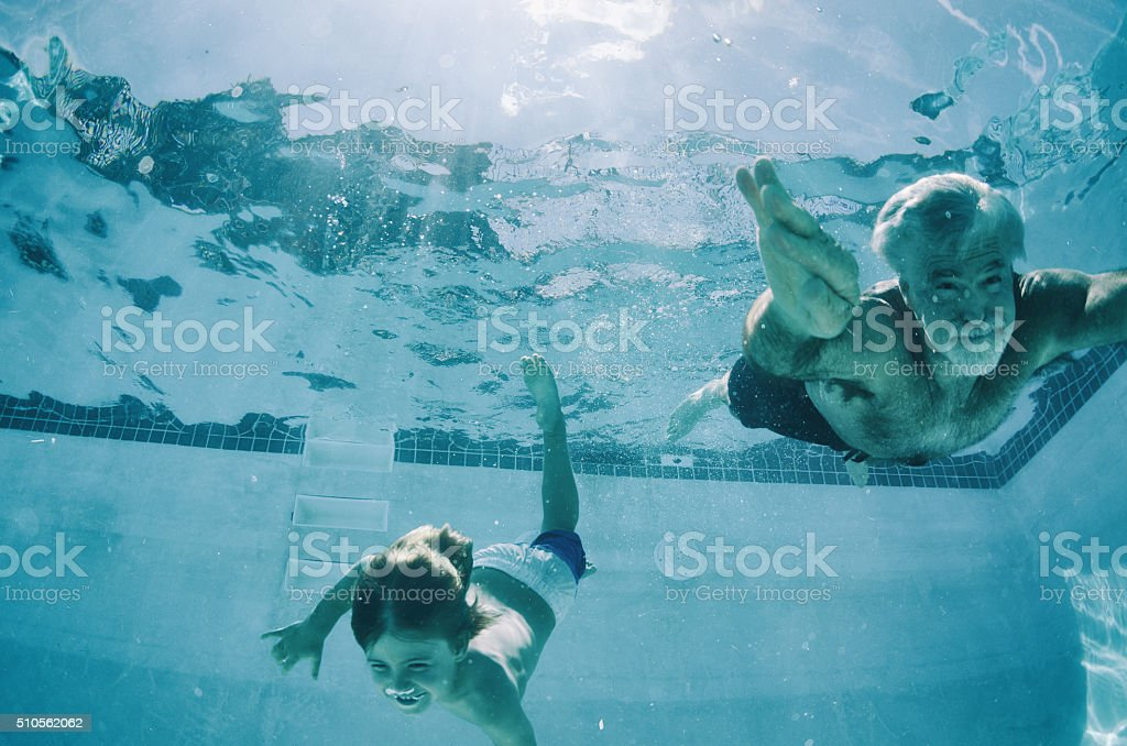 Grandpa and Grandson swimming underwater in summer stock photo