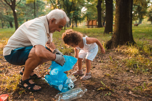 Grandpa and his granddaughter keeping the environment clean stock photo