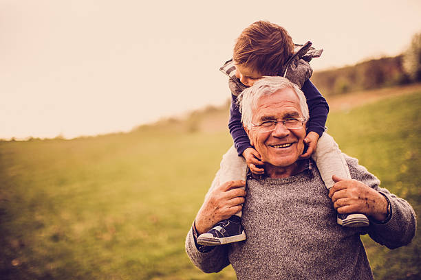 Grandpa and me Photo of  little boy with his grandfather, enjoying in the amazing nature. Grandfather is carrying him on his shoulders. grandson stock pictures, royalty-free photos & images