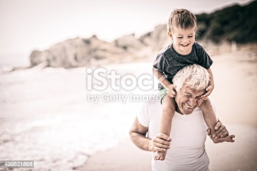 Little smiling boy is spending summer vacation with his grandfather by the sea