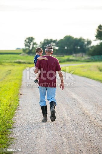Rear view of a grandfather carrying his two year old grandson as they walk down a rural gravel driveway on a summer evening.