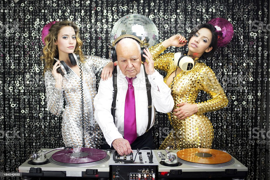 grandpa DJ and two beautiful gogo dancers stock photo