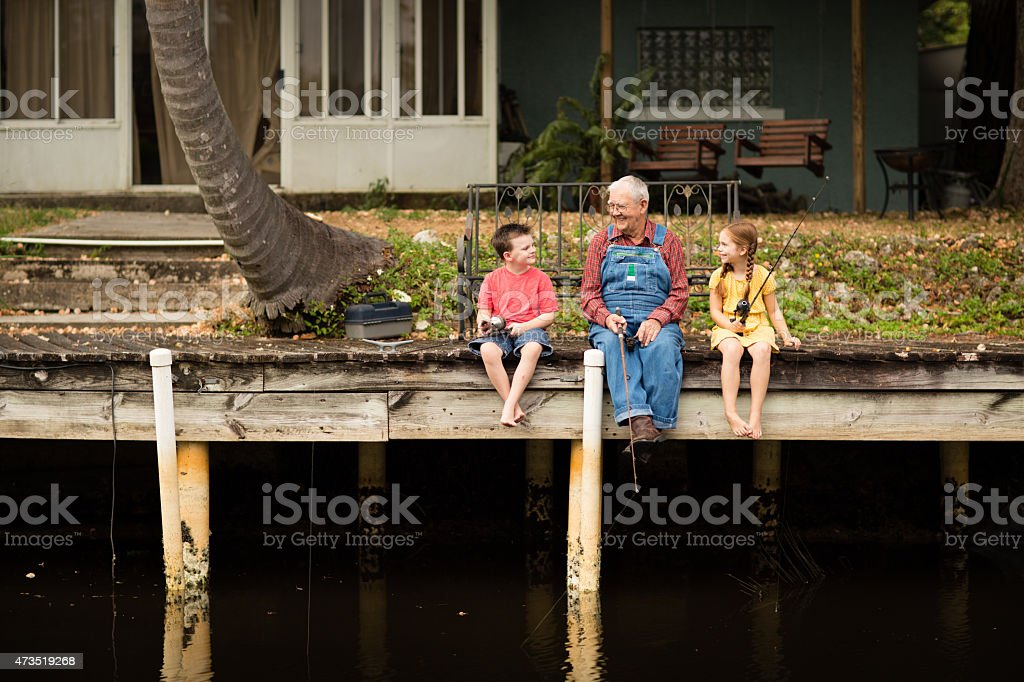 Grandpa Fishing on Dock with Great Grandson and Granddaughter stock photo