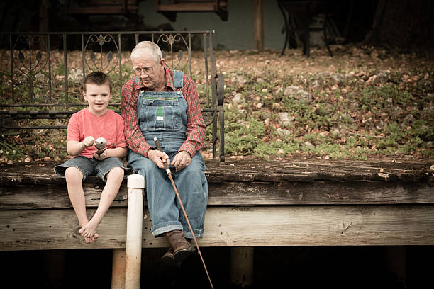 Grandpa Fishing With His Great Grandson on Wood Dock Color image of a senior man sitting on an old, wooden dock while fishing with his young great grandson. bib overalls boy stock pictures, royalty-free photos & images