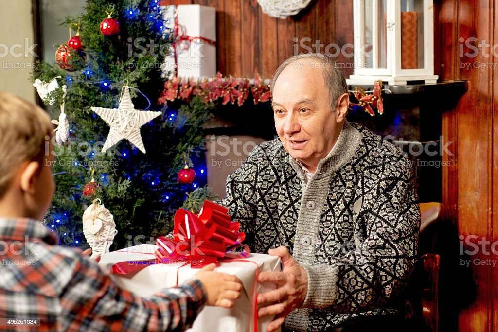 Grandpa giving a Gift to Grandson stock photo