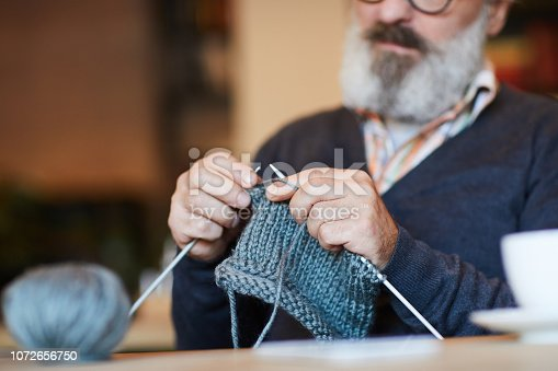 Bearded grandpa knitting warm woolen sweater or other knitwear at lesiure