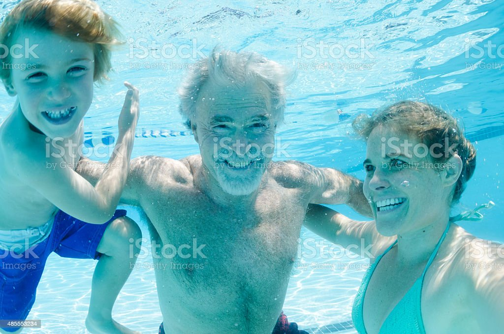 Grandpa, mother, and son swimming together, underwater stock photo