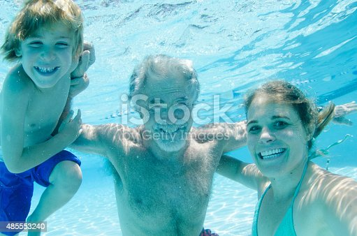 596350174istockphoto Grandpa, mother, and son swimming together, underwater smiling 485553240