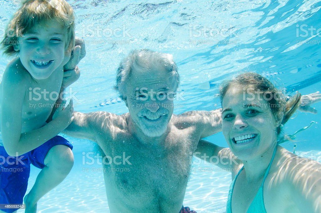 Grandpa, mother, and son swimming together, underwater smiling stock photo