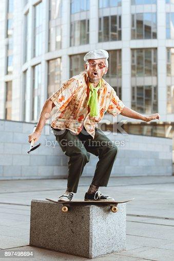 istock Grandpa on a skateboard is jumping. 897498694