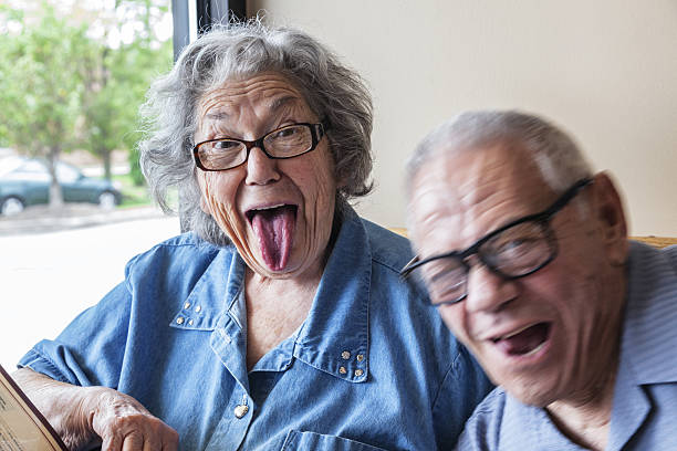 grandpa photo bombing grandma making funny tongue wagging face - funny fat lady stock photos and pictures