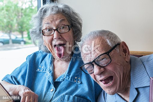 A crazy octogenarian senior adult married husband and wife are mugging for the camera in a restaurant. Grandpa is photo bombing Grandma as she sticks her tongue out making a goofy, exaggerated tongue hanging out face.