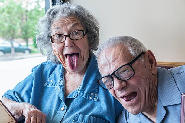 Grandpa Photo Bombing Grandma's Funny Tongue Wagging Face stock photo