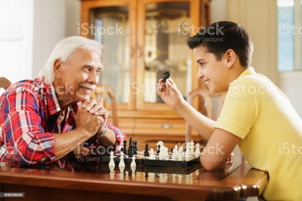 Happy little kid playing chess with senior man at home. Family...